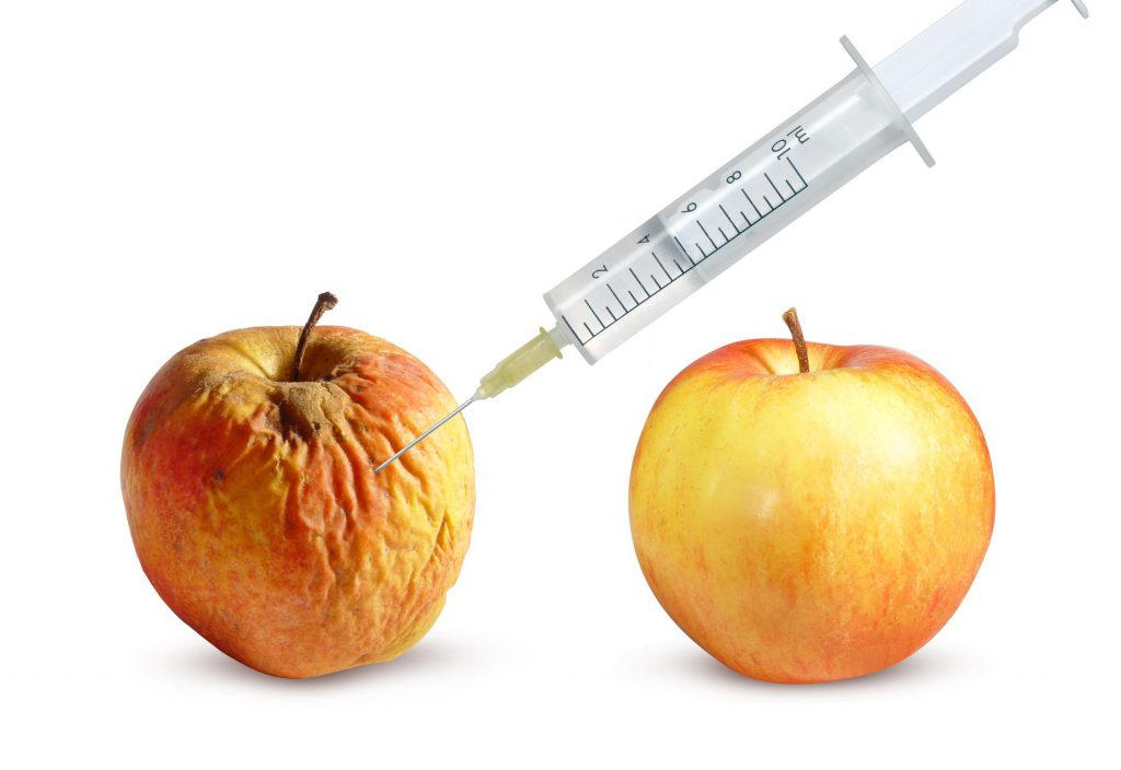 Wrinkled apple and a nice apple and syringe on a white background